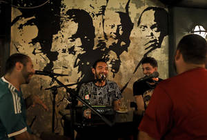 Photo - In this Monday, July 7, 2014 photo, Filipino Syrian rapper Nasser Shorbaji, 29, center, and Lebanese Marwan Alameh, 32, second right, laugh during a live broadcast of their show 'Bar Fight' at Radio Beirut, in Lebanon. The duo are among a host of Lebanese graffiti artists and rappers trying to re-engage disaffected youth in a debate about the country's latest wave of political turmoil and the woes of the greater Middle East. (AP Photo/Bilal Hussein)