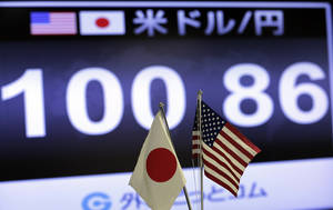 Photo - A screen indicates the current exchange rate of the U.S. dollar against Japanese yen behind the both countries' flags at a foreign exchange company in Tokyo, Friday,  May 10, 2013.(AP Photo/Itsuo Inouye)