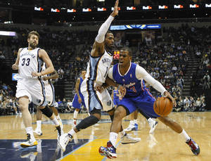 Photo - Los Angeles Clippers guard Chris Paul (3) goes to the basket against Memphis Grizzlies guard Mike Conley (11) and center Marc Gasol (33), of Spain, in the first half of an NBA basketball game Friday, Feb. 21, 2014, in Memphis, Tenn. (AP Photo/Lance Murphey)