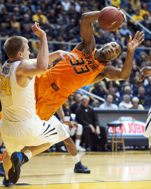 Photo - Oklahoma State's Marcus Smart, right, collides with West Virginia's Kevin Noreen during the first half of an NCAA college basketball game Saturday, Jan. 11, 2014, in Morgantown, W.Va. (AP Photo/Andrew Ferguson)