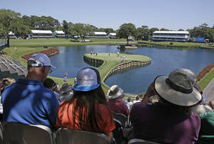 Photo - Spectators watch golfers on the 17th green during a practice round for The Players championship golf tournament at TPC Sawgrass in Ponte Vedra Beach, Fla., Tuesday, May 6, 2014. (AP Photo/John Raoux)