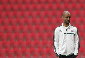 Photo - FC Bayern Munich's head coach Pep Guardiola observes his players during a  training session for the Super Cup soccer match, at the Eden stadium in Prague, Czech Republic, Thursday, Aug. 29, 2013. Munich will play Chelsea in a Super Cup soccer match on Friday. (AP Photo/Petr David Josek)