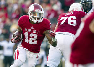 Photo - Indiana's Stephen Houston (12) looks for the hole in the Purdue defense and rushes the ball into the end zone for a touchdown during the first half of an NCAA college football game Saturday, Nov. 30, 2013, in Bloomington, Ind. (AP Photo/Doug McSchooler)