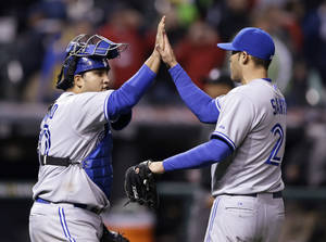 Photo - Toronto Blue Jays' Dioner Navarro, left, and Sergio Santos celebrate after the Blue Jays defeated the Cleveland Indians 3-2 in a baseball game, Friday, April 18, 2014, in Cleveland. (AP Photo/Tony Dejak)