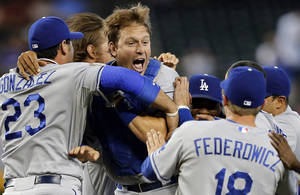 Photo - The Los Angeles Dodgers celebrate a 7-6 win over the Arizona Diamondbacks in a baseball game on Thursday, Sept. 19, 2013, in Phoenix. The Dodgers clinched the National League West title. (AP Photo/Matt York)