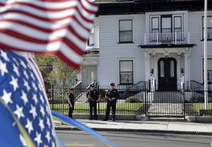 Photo - Police keep watch outside Graham, Putnam, and Mahoney Funeral Parlors in Worcester, Mass., Monday, May 6, 2013 where the body of killed Boston Marathon bombing suspect Tamerlan Tsarnaev is being prepared for burial. Funeral director Peter Stefan has pleaded for government officials to use their influence to convince a cemetery to bury Tsarnaev, but so far no state or federal authorities have stepped forward. (AP Photo/Elise Amendola)