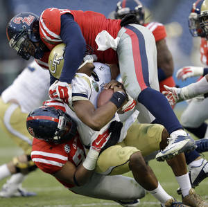 Photo - Georgia Tech quarterback Vad Lee is brought down by Mississippi defenders Issac Gross, bottom, and Robert Nkemdiche, top, in the second quarter of the NCAA college football Music City Bowl game on Monday, Dec. 30, 2013, in Nashville, Tenn. (AP Photo/Mark Humphrey)