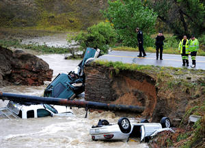 "Photo - Emergency officials investigate a road collapse Thursday on U.S. 287 and Dillon Road northwest of Denver. Flash flooding caused the cave-in, sending three vehicles into the water. The National Weather Service has warned of an ""extremely dangerous and life-threatening situation"" in the region. AP Photo"