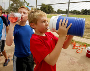 photo - Zachary Gillum, 10, left, and Cameron Norman, 9, take a water break Tuesday during the city-sponsored Speed and Agility Camp in Norman.