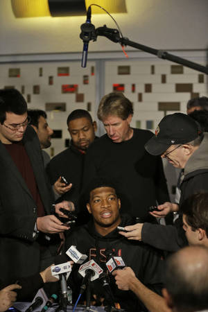 Photo - Heisman Trophy finalist Jameis Winston, center, a quarterback at Florida State, talks to  reporters during an informal media availability, Friday, Dec. 13, 2013, in New York. (AP Photo/Julio Cortez)