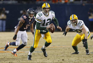 Photo - Green Bay Packers quarterback Aaron Rodgers (12) scrambles as he looks for a receiver during the first half of an NFL football game against the Chicago Bears, Sunday, Dec. 29, 2013, in Chicago. (AP Photo/Charles Rex Arbogast)