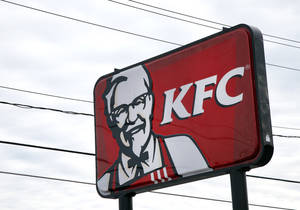 Photo - In this  Friday, Jan. 31, 2014, photo, a KFC sign hangs in Saugus, Mass. Fast-food conglomerate Yum! Brands, Inc., headquartered in Louisville, Ky., will report its fourth-quarter and annual earnings on Monday after markets close. (AP Photo/Elise Amendola)