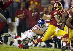 Photo - New York Giants defensive end Osi Umenyiora (72) reaches for Washington Redskins quarterback Robert Griffin III (10) during the first half of an NFL football game in Landover, Md., Monday, Dec. 3, 2012. (AP Photo/Evan Vucci)