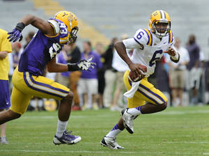 Photo - LSU quarterback Brandon Harris (6) turns the corner to get outside past the pursuit of defensive end Michael Patterson (93) at the NCAA college football Spring Game in Baron Rouge, La., Saturday, April 5, 2014. (AP Photo/The Baton Rouge Advocate, Travis Spradling) NO SALES; MAGAZINES OUT; INTERNET OUT; TV OUT; FOREIGN OUT; LOUISIANA BUSINESS INC. OUT (INCLUDING GREATER BATON ROUGE BUSINESS REPORT; 225; 10/12; INREGISTER; LBI CUSTOM OUT; MANDATORY CREDIT THE ADVOCATE