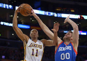 Photo - Los Angeles Lakers guard Wesley Johnson, left, has his shot blocked by Philadelphia 76ers center Spencer Hawes during the first half of an NBA basketball game, Sunday, Dec. 29, 2013, in Los Angeles. (AP Photo/Mark J. Terrill)