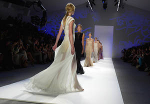 Photo -   Models walk in the finale of the Tadashi Shoji Spring 2013 collection during Fashion Week in New York, Thursday, Sept. 6, 2012. (AP Photo/Richard Drew)