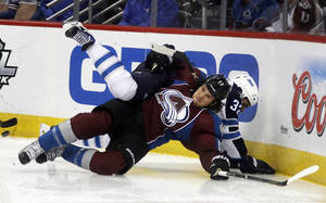 Photo - Colorado Avalanche right wing Steve Downie, front, gets tangled up with Winnipeg Jets defenseman Dustin Byfuglien while fighting for control of the puck in the second period of an NHL hockey game in Denver on Sunday, Oct. 27, 2013. (AP Photo/David Zalubowski)