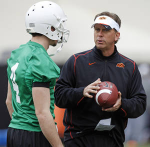 photo - OSU offensive coordinator and quarterbacks coach Todd Monken talks to J.W. Walsh during Oklahoma State spring football practice at Boone Pickens Stadium in Stillwater, Okla., Monday, March 7, 2011. Photo by Nate Billings, The Oklahoman