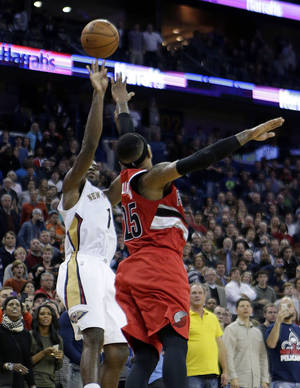 Photo - New Orleans Pelicans guard Tyreke Evans (1) shoots the game-winning shot over Portland Trail Blazers guard Mo Williams (25) in the final seconds of the second half of an NBA basketball game in New Orleans, Monday, Dec. 30, 2013. The Pelicans won 110-108. (AP Photo/gerald herbert)