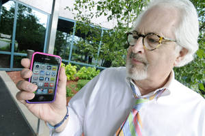 Photo -   Bob Burns holds his smartphone Wednesday, June 27, 2012 in Minnetonka, Minn. Millions of smartphone users wiil soon begin receiving text messages about severe weather from a sophisticated government system that can send a blanket warning to mobile devices in the path of a dangerous storm. (AP Photo/Jim Mone)