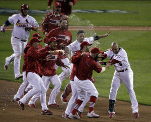 Photo - St. Louis Cardinals' Carlos Beltran is mobbed by teammates after his game-winning hit during the 13th inning of Game 1 of the National League baseball championship series against the Los Angeles Dodgers Saturday, Oct. 12, 2013, in St. Louis. (AP Photo/Chris Carlson)