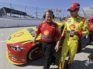 Photo - Joey Logano, right, talks with crew chief Todd Gordon during qualifying for Sunday's NASCAR Sprint Cup auto race at Martinsville Speedway in Martinsville, Va., Friday, April 5, 2013.  (AP Photo/Steve Helber)