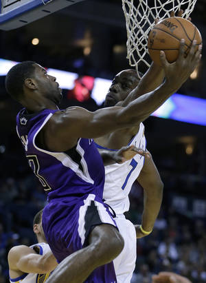 Photo - Sacramento Kings' Tyreke Evans, left, shoots against Golden State Warriors' Carl Landry (7) during the first half of an NBA basketball game Wednesday, March 27, 2013, in Oakland, Calif. (AP Photo/Ben Margot)