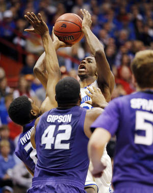 Photo - Kansas guard Andrew Wiggins, back, shoots over Kansas State defenders Wesley Iwundu, left, Thomas Gipson (42) and Will Spradling (55) during the first half of an NCAA college basketball game in Lawrence, Kan., Saturday, Jan. 11, 2014. (AP Photo/Orlin Wagner)