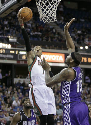 photo - Milwaukee Bucks guard Monta Ellis, left, drives to the basket against Sacramento Kings  center DeMarcus Cousins, right, during the first quarter of  an NBA basketball game in Sacramento, Calif., Sunday, March 10, 2013.(AP Photo/Rich Pedroncelli)