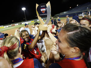 photo - Rhea Taylor (3), left holding trophy, and other members of Team USA celebrate with the championship trophy after the championship game of the World Cup of Softball between the United States and Australia at ASA Hall of Fame Stadium in Oklahoma City, Monday, July 2, 2012. The USA won, 3-0. Photo by Nate Billings, The Oklahoman