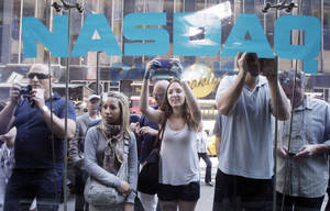 Photo -   FILE - In a Friday, May 18, 2012 file photo, curious bystanders watch through the Nasdaq windows as Facebook shares begin trading, in New York. Facebook's stock is sinking nearly 7 percent, Monday, May 21, 2012, falling below the $38 IPO price, in the social network's second day of trading as a public company. (AP Photo/Richard Drew, File)