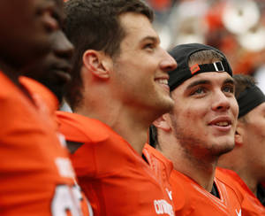 photo - OSU quarterback J.W. Walsh, far right, sings the alma mater with teammates the Cowboys' 65-24 victory over Louisiana-Lafayette Saturday, Sept. 15, 2012, at Boone Pickens Stadium in Stillwater, Okla. The Fox Sports broadcast team for the game lauded Walsh's performance in relief of injured starter Wes Lunt. Photo by Nate Billings, The Oklahoman