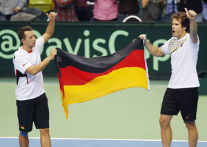 Photo - Germany's double Philipp Kohlschreiber, left, and Tommy Haas celebrate with the German flag after beating Spain's Fernando Verdasco and David Marrero during a Davis Cup World Group first round tennis match between Germany and Spain in Frankfurt, Germany, Saturday, Feb. 1, 2014. After winning the double, Germany has now a 3-0 lead and advances to the next round. (AP Photo/Michael Probst)