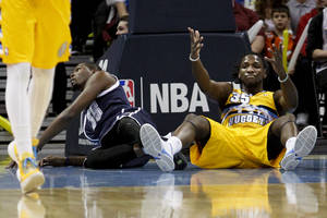 Photo - Denver Nuggets' Kenneth Faried, right, reacts after fouling Oklahoma City Thunder's Kevin Durant, left, during the first quarter of an NBA basketball game, Thursday, Jan. 9, 2014, in Denver. (AP Photo/Barry Gutierrez)