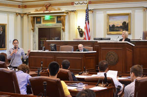 Photo - Morgan Brun, an Oklahoma State University student, speaks during a mork legislative debate at the state Capitol, held as part of the recent Muslim Youth Leadership Symposium hosted by the Council on American-Islamic Relations-Oklahoma chapter. State Rep. Emily Virgin, D-Norman, is seated at the upper right. Photo provided <strong></strong>
