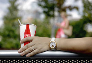 Photo - FILE - In this Monday, July 16, 2012, file  photo, a consumer sits outside the entrance to the World of Coca Cola attraction in Atlanta. The Coca-Cola Co. is expected to report quarterly earnings on Tuesday, Oct. 15, 2013. (AP Photo/David Goldman, File)