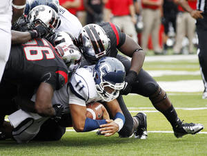 Photo -   Connecticut quarterback Scott McCummings (11) holds onto the ball as he is tackled by Rutgers defenders during the first half of an NCAA college football game in Piscataway, N.J., Saturday, Oct. 6, 2012. (AP Photo/Mel Evans)