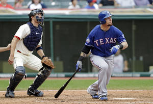 photo - FILE - In this Dec. 2, 2012, file photo, Texas Rangers&#039; Josh Hamilton watches his home run with Cleveland Indians catcher Lou Marson during a baseball game in Cleveland. Rangers general manager Jon Daniels said Thursday, Dec. 13, 2012, that Hamilton has agreed to a contract with the Los Angeles Angels. (AP Photo/Mark Duncan, File)