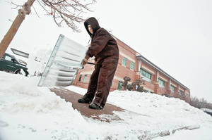 Photo - Left: John McBride uses a shovel Friday  to clear the sidewalks and parking lots of ice and snow at Integris Canadian Valley Hospital  in Yukon. Photo by Chris Landsberger, The Oklahoman   Online: To watch videos that show how Oklahomans coped with Friday's stormy weather, go to NewsOK.com/news/severeweather.