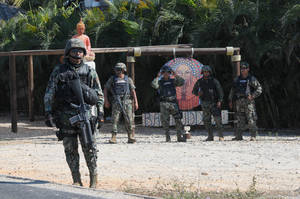 Photo - Mexican navy marines stand at a roadblock due to stepped up security after masked armed men broke into a beach home, raping six Spanish tourists who had rented the house in Acapulco, Mexico, Tuesday Feb. 5, 2013. According to the Mayor of Acapulco, five masked men burst into a house the Spaniards had rented on the outskirts of Acapulco, in a low-key area near the beach, and held a group of six Spanish men and one Mexican woman at gunpoint, while they raped the Spanish women before dawn on Monday. (AP Photo/Bernandino Hernandez)