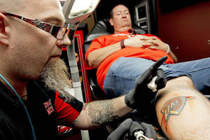 photo - Chris Zamorano, of Oklahoma City, gets a free Thunder tattoo Friday from Josh Poindexter at Tornado Tattoos in Oklahoma City. Photos by Bryan Terry, The Oklahoman