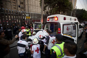 photo - An injured person is carried into an ambulance after an explosion at an adjacent building to the executive tower of Mexico's state-owned oil company PEMEX, in Mexico City, Thursday Jan. 31, 2013. An explosion at the main headquarters of Mexico's state-owned oil company in the capital killed more than 10 people and injured some 80 as it heavily damaged three floors of the building, sending hundreds into the streets and a large plume of smoke over the skyline. (AP Photo/Eduardo Verdugo)