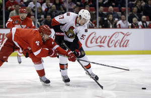 Photo - Detroit Red Wings defenseman Jakub Kindl (4) of the Czech Republic and Ottawa Senators center Derek Grant (57) reach for the puck during the first period of an NHL hockey game in Detroit, Saturday, Nov. 23, 2013. (AP Photo/Carlos Osorio)