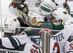 Photo - Minnesota Wild's Nino Niederreiter, center,  of Switzerland, is mobbed by teammates after he scored the winning goal off Nashville Predators goalie Carter Hutton  in overtime of an NHL hockey game, Thursday, Feb. 6, 2014, in St. Paul, Minn. The Wild won 3-2. (AP Photo/Jim Mone)