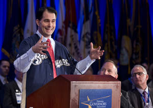 photo - Wisconsin Gov. Scott Walker, left, sporting his state's Major League Baseball team the Milwaukee Brewers' team jersey, sends his invitation to the delegates of the National Governors Association 2013 Winter Meeting in Washington, Saturday, Feb. 23, 2013, inviting them for the next NGA meeting to the host state and to watch the Brewers' game. Seated, from center to right, are NGA Chairman Gov. Jack Markell of Delaware and Walgreens CEO and President Gregory Wasson.  (AP Photo/Manuel Balce Ceneta)