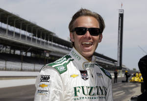 Photo - Pole-sitter Ed Carpenter laughs as he watches Dario Franchitti squeal the tires on the pace car as he pulled onto the track before the start of practice for the Indianapolis 500 IndyCar auto race at the Indianapolis Motor Speedway in Indianapolis, Monday, May 19, 2014. (AP Photo/Michael Conroy)