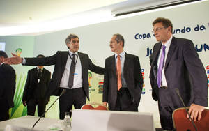 Photo -   FIFA Director of Communications Walter De Gregorio, left, asks Brazil's Sports Minister Aldo Rebelo, center, to step down from the stage as FIFA General Secretary Jerome Valcke, right, waits for the start of a news conference in Rio de Janeiro, Brazil, Wednesday, May 30, 2012. (AP Photo/Victor R. Caivano)