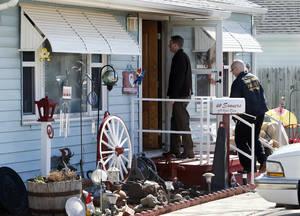 Photo - Investigators examine the scene of a house fire Wednesday in Norman. Photo by Steve Sisney, The Oklahoman