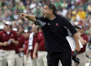Photo - FILE - In this Aug. 31, 2013, file photo, Temple coach Mark Rhule yells to his team during an NCAA college football game against Notre Dame in South Bend, Ind. Rhule shares some of the safety concerns held by Arkansas' Bret Bielema and Alabama's Nick Saban about how hurry-up offenses increase the number of plays per game and don't allow defenses to substitute for fatigued players. Rhule said it's better to be out in front of a potentially dangerous situation than too late. (AP Photo/Michael Conroy, File)