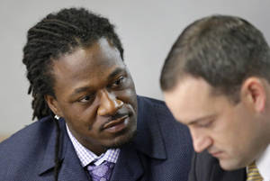 Photo - Adam Jones, left, cornerback for the NFL football Cincinnati Bengals, talks with attorney Chad Ziepfel during his assault trial, Monday, Oct. 7, 2013, in Cincinnati. Jones is charged with assaulting a woman at a nightclub. (AP Photo/Al Behrman)
